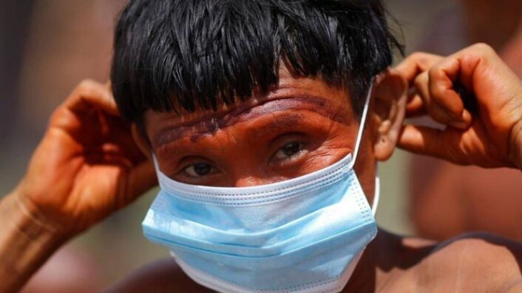 88669972_a-man-from-the-indigenous-yanomami-ethnic-group-holds-his-protective-face-mask-amid-the-spr